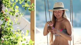 Mujer rubia imponente que se sienta en un oscilación en la playa metrajes