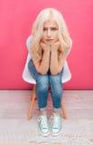 Mujer rubia infeliz que se sienta en la silla Imagenes de archivo