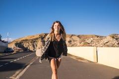 Mujer rubia joven agradable que camina con la sonrisa del monopatín Foto de archivo libre de regalías