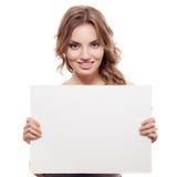 Mujer rubia joven alegre que lleva a cabo un espacio en blanco blanco Foto de archivo