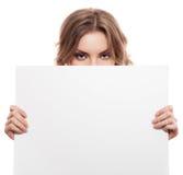 Mujer rubia joven alegre que lleva a cabo un espacio en blanco blanco Foto de archivo libre de regalías