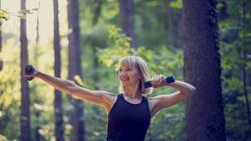 Mujer rubia joven apta que se resuelve con pesas de gimnasia afuera imágenes de archivo libres de regalías