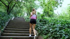 Mujer rubia joven atlética atractiva hermosa en una camiseta y los pantalones cortos, funcionamientos arriba, en el bosque, parqu metrajes