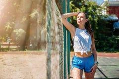 Mujer rubia joven atlética que descansa sobre campo de deportes durante sus vacaciones de entrenamientos fotografía de archivo