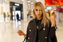 Mujer rubia joven atractiva elegante con los ojos grises en una capa gris elegante en una camisa de moda negra con un bolso negro imágenes de archivo libres de regalías