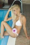 Mujer rubia joven atractiva en bikiní por la piscina Imagen de archivo