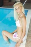 Mujer rubia joven atractiva en bikiní por la piscina Fotos de archivo