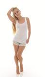 Mujer rubia joven atractiva en el top sin mangas y los pantalones cortos blancos Imágenes de archivo libres de regalías