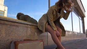 Mujer rubia joven atractiva en foso con la maleta del vintage en la estación marina almacen de video
