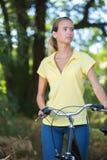 Mujer rubia joven atractiva en la bici Imagen de archivo libre de regalías