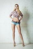 Mujer rubia joven atractiva en pantalones cortos de los tejanos Imagenes de archivo