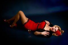 Mujer rubia joven atractiva en una alineada roja en un negro fotografía de archivo