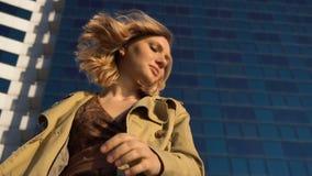Mujer rubia joven atractiva en zapatos del foso y del tacón alto con la maleta del vintage en la estación marina, con arriba azul almacen de video