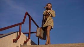 Mujer rubia joven atractiva en zapatos del foso y del tacón alto con la maleta del vintage que va abajo al embarcadero de Jacht almacen de metraje de vídeo