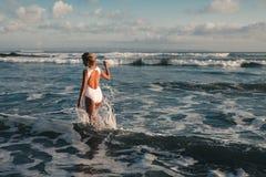 Mujer rubia joven atractiva que camina en la playa Fotografía de archivo