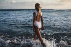 Mujer rubia joven atractiva que camina en la playa Imagen de archivo libre de regalías