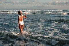 Mujer rubia joven atractiva que camina en la playa Fotos de archivo