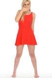 Mujer rubia joven chocada atractiva atractiva que lleva a Mini Dress rojo corto Imágenes de archivo libres de regalías