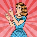 Mujer rubia joven chocada que sostiene el teléfono móvil Arte pop Fotos de archivo libres de regalías