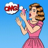Mujer rubia joven chocada que sostiene el teléfono móvil Arte pop Fotografía de archivo libre de regalías