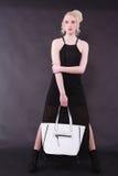 Mujer rubia joven con el bolso blanco Fotos de archivo