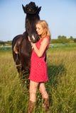 Mujer rubia joven con el caballo Imagen de archivo