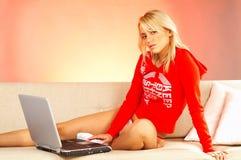 Mujer rubia joven con el ordenador portátil. Fotografía de archivo