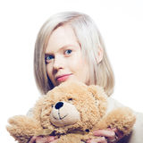 Mujer rubia joven con el oso de peluche Imagenes de archivo