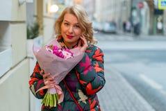 Mujer rubia joven con el ramo de las flores en una calle de la ciudad Fotografía de archivo libre de regalías