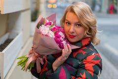 Mujer rubia joven con el ramo de las flores en una calle de la ciudad Fotos de archivo libres de regalías