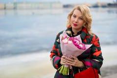 Mujer rubia joven con el ramo de las flores en una calle de la ciudad Fotos de archivo