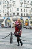 Mujer rubia joven con el ramo de las flores en una calle de la ciudad Imagenes de archivo