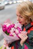 Mujer rubia joven con el ramo de las flores en una calle de la ciudad Imagen de archivo