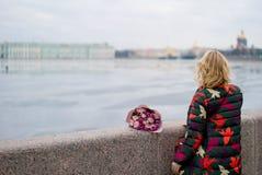 Mujer rubia joven con el ramo de las flores en una calle de la ciudad Imágenes de archivo libres de regalías