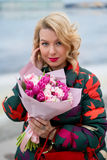Mujer rubia joven con el ramo de las flores en una calle de la ciudad Imagen de archivo libre de regalías