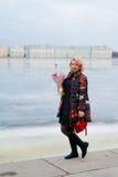 Mujer rubia joven con el ramo de las flores en una calle de la ciudad Foto de archivo libre de regalías