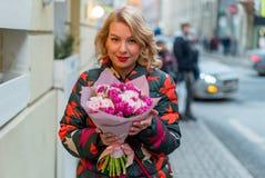 Mujer rubia joven con el ramo de las flores en una calle de la ciudad Foto de archivo