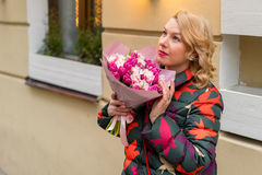 Mujer rubia joven con el ramo de las flores en una calle de la ciudad Fotografía de archivo