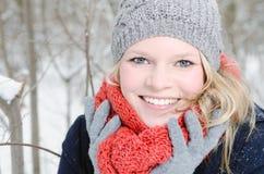 Mujer rubia joven con el retrato de madera del invierno de la gorrita tejida y de la bufanda Imagenes de archivo