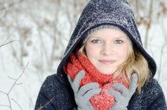 Mujer rubia joven con el retrato de madera del invierno de la gorrita tejida y de la bufanda Imágenes de archivo libres de regalías