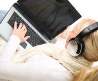 Mujer rubia joven con la computadora portátil y los auriculares. Imagen de archivo libre de regalías