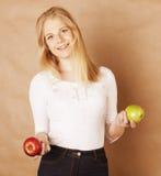 Mujer rubia joven con la manzana verde y roja, buena Imagenes de archivo