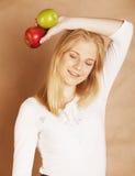 Mujer rubia joven con la manzana verde y roja, buena Imágenes de archivo libres de regalías