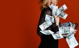 Mujer rubia joven con la pila de ganador afortunado del dinero en rojo foto de archivo libre de regalías