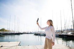Mujer rubia joven con la tableta digital al aire libre Imagen de archivo libre de regalías