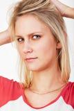 Mujer rubia joven con las manos en su pelo Fotos de archivo libres de regalías