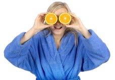 Mujer rubia joven con los halfs de la naranja Fotos de archivo