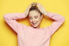 Mujer rubia joven con los ojos cerrados, sobre fondo amarillo Imágenes de archivo libres de regalías