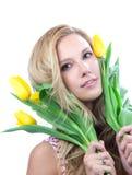 Mujer rubia joven con los tulipanes amarillos del resorte Foto de archivo libre de regalías