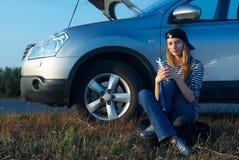 Mujer rubia joven con su coche quebrado Fotos de archivo